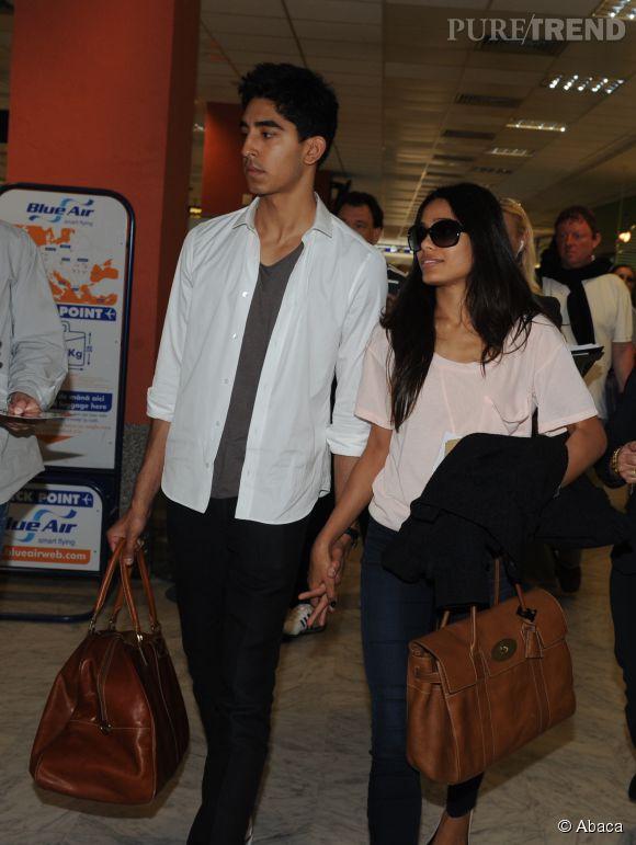 Lorsqu'il quittent Cannes après le festival, Dev Patel et Freida Pinto arrivent main dans la main et assortis à l'aéroport de Nice : haut clair sac de voyage en cuir pour les deux.