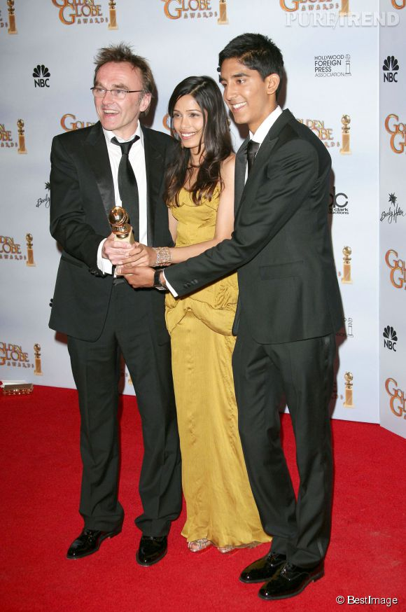 """Le 11 janvier 2009, """"Slumdog Millonaire"""" reçoit quatre Golden Globes, qui seront suivis de huit Oscars. Dev et Freida partagent leur joie sur tapis rouge avec le réalisateur, Danny Boyle."""