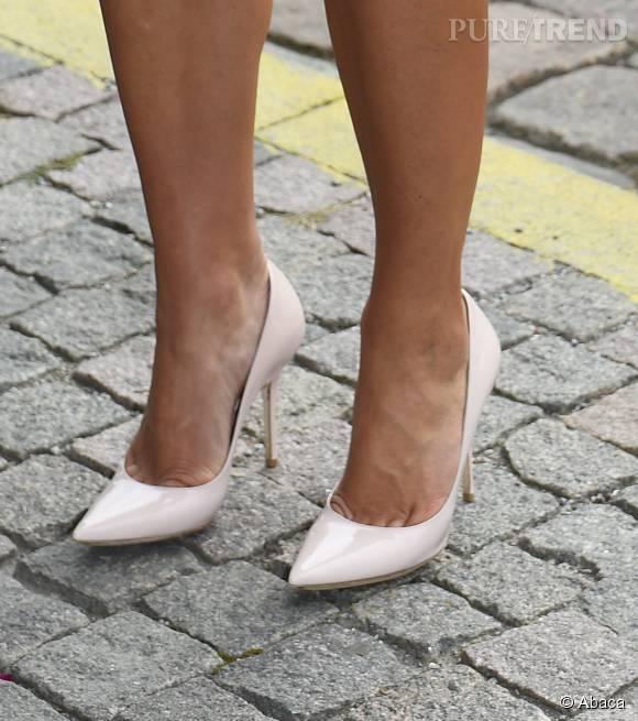 Toujours parfaitement coordonnée, elle prend de la hauteur sur une paire d'escarpins blancs.