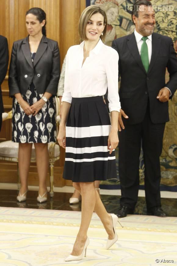 En chemisier blanc et jupe taille haute, elle fait un sans-faute.