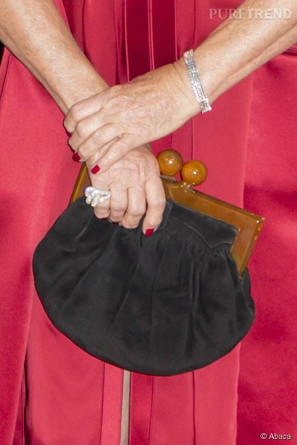 Catherine Deneuve s'est aussi équipée d'une pochette à fermoir au style rétro.