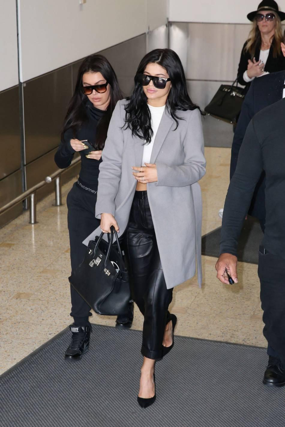 Kylie Jenner à son arrivée à Sydney, mardi. Manteau gris et escarpins pour un look chic.