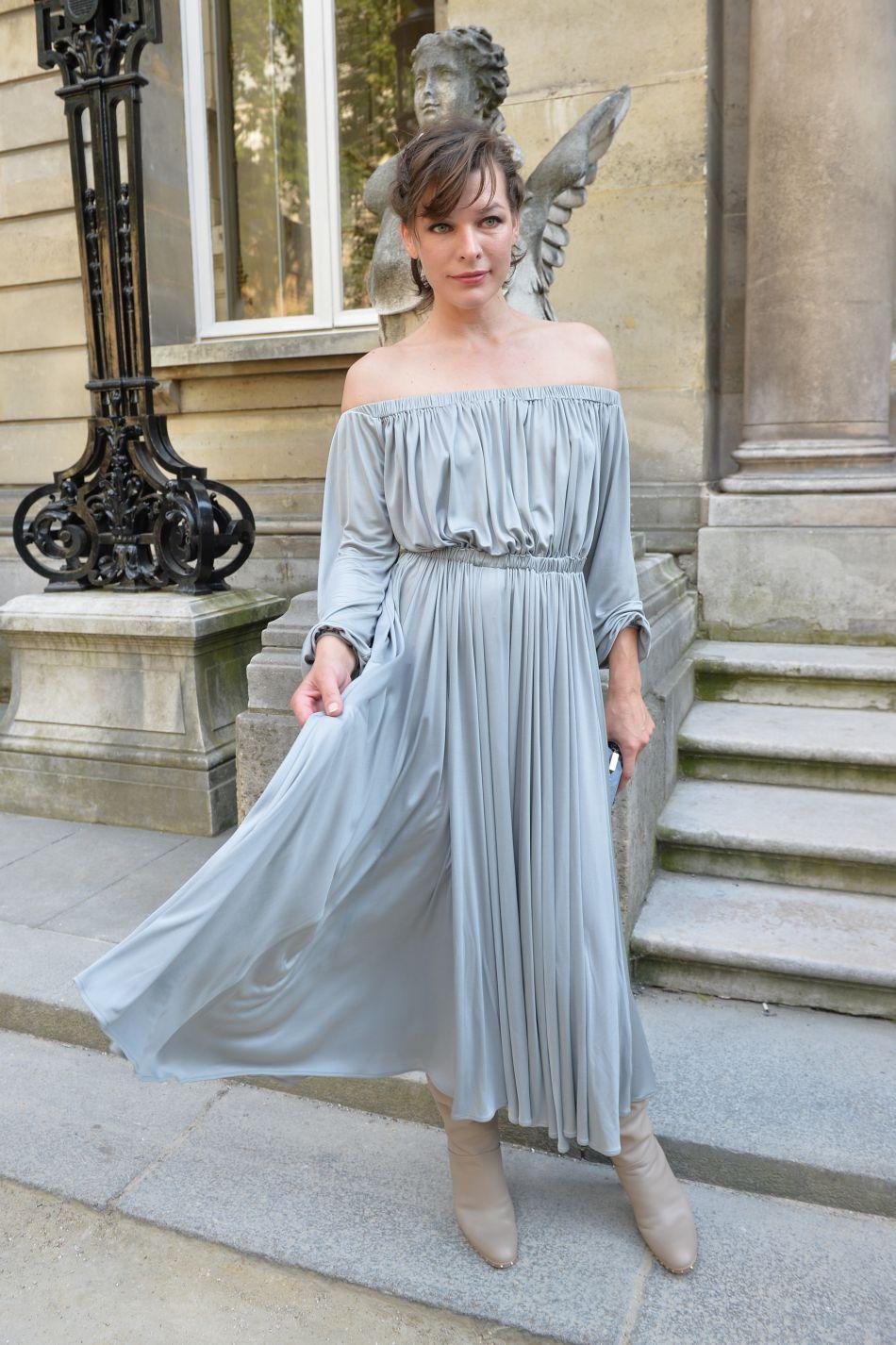 Mila Jovovich porte une robe grise parfaitement dans le thème.