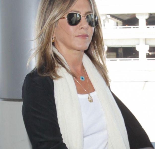 Jennifer Aniston ressort ses basiques : jean slim, top blanc et sandales compensées.