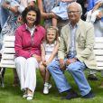 La reine Silvia, la princesse Estelle et le roi Carl Gustav de Suède, entre eux deux, la plus âgée de leurs petits-enfants, la princesse Estelle.