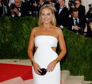 Dans cette robe blanche ajourée Calvin Klein, Margot Robbie met en valeur sa peau hâlée.