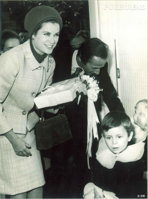 La Princesse Grace de Monaco portant le tailleur San Fransico de Marc Bohan pour Dior, lors de l'inauguration de la Boutique Baby Dior en 1967, auprès de Marc Bohan et du petit Hubert de Chalmeton de Croy.