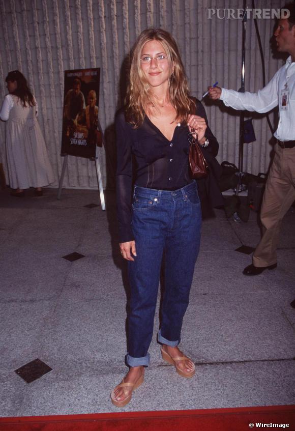 Wedges aux pieds, lunettes de vue sur le nez, Jennifer Aniston ose le chemisier transparent rentré dans un jean droit, taille haute. C'etait certainement tendance en 1998.