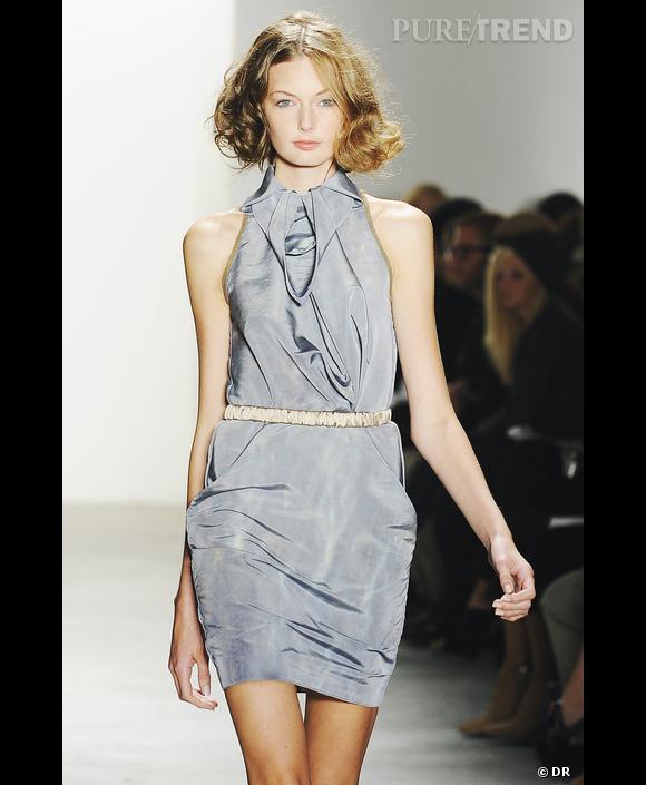 Costello Tagliapietra , Défilé Printemps-Eté 2010, New York      Une robe de Costello Tagliapietra gris argenté soulignée d'une ceinture cristal. Grâce à l'effet moiré et scintillant, le gris tourterelle se fait léger et heureux. Il met en valeur le regard gris bleu et la peau rosée du modèle, faisant ressortir toute la lumière de ses cheveux blonds.