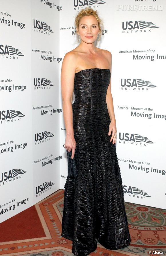 Kim Cattrall en noir  Quelle élégance ! Le noir, surtout dans la version irisée de cette robe floquée aux épaules dénudées, met en valeur la peau claire de Kim Catrall et fait résonner la lumière, blond doré, de ses cheveux.