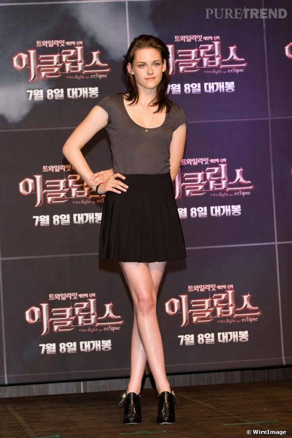 """Pour promouvoir Twilight à Séoul, Kristen Stewart opte pour une jupe DKNY qu'elle glamourise d'une paire d'ankle boots, évitant le côté """"scolaire"""" avec un top échancré."""