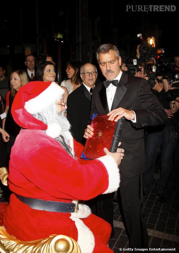 Père Noël ou pas, George Clooney s'en fiche et essaie de lui arracher des  mains son livre de listes de Noël. Pas très gentleman George, de piquer les cadeaux de tous les enfants. Peut-être en a t-il ras la capsule de sa machine à café...