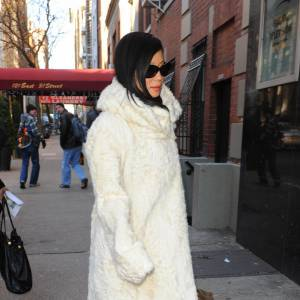 Lucy Liu version Cruella d'Enfer en long manteau blanc.