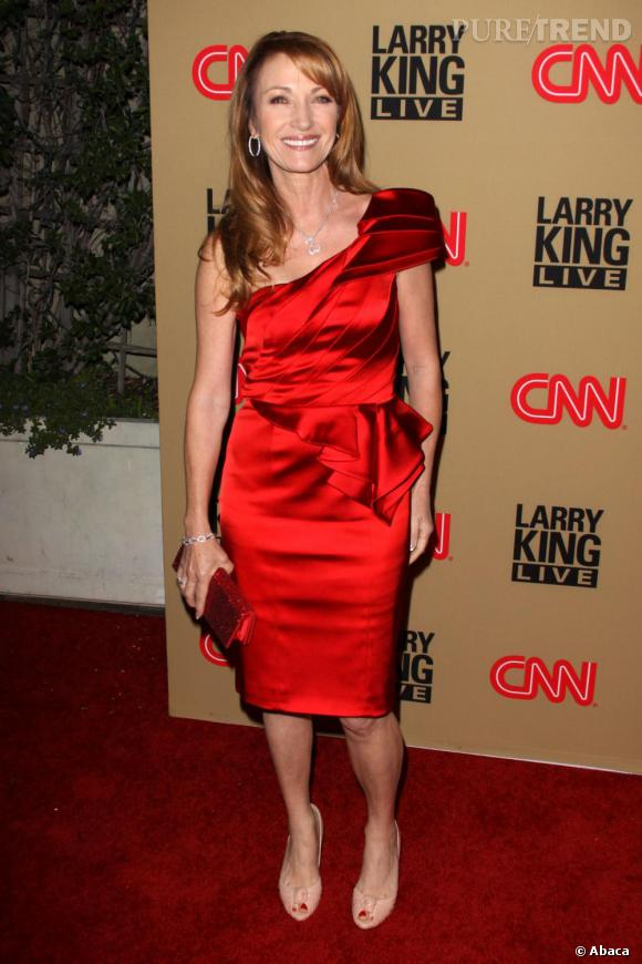 En accord avec le red capet, l'actrice mise sur une robe de cocktail rouge et s'offre encore un peu plus de glamour avec des bijoux brillants.