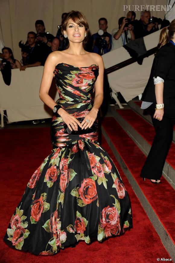 Pochette satinée et dotée d'un noeud XXL, Eva Mendes joue la carte printanière moulée dans une robe fourreau imprimée de roses.