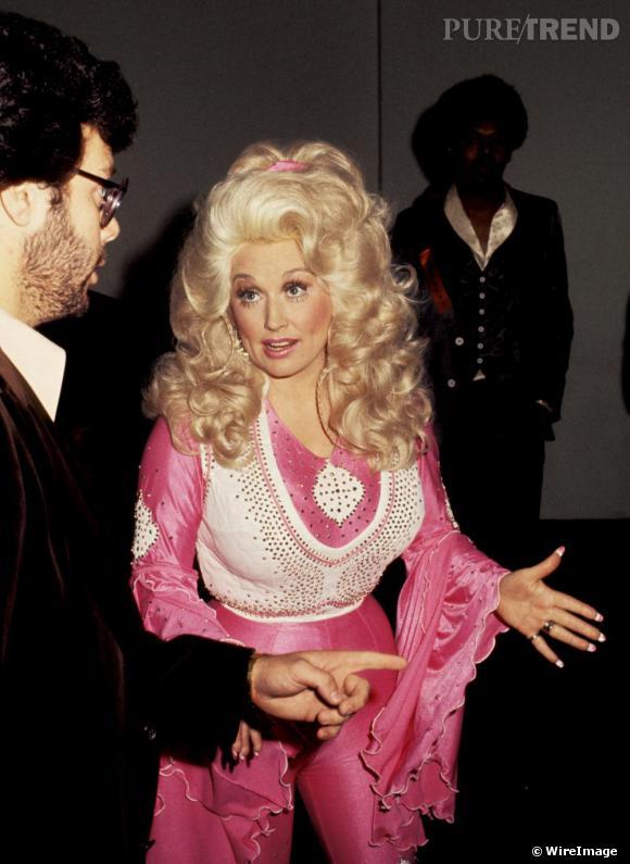 Avant Taylor Swift, la reine de la country, c'était Dolly Parton. En 1977, c'est dans une combinaison rose et blanche à paillettes qu'une Dolly très chouchroutée foule le red carpet.