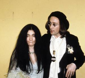 John Lennon et Yoko Ono qui joue les oiseaux des îles avec un boa à longues plumes.