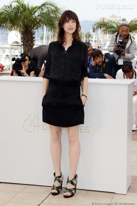 L'actrice porte une robe sobre et noire qu'elle dédramatise avec des sandales vertes.