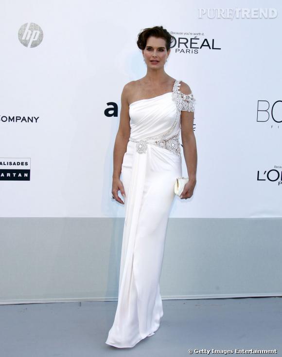 Brooke Shields flatte sa carnation à l'aide d'une robe blanche.