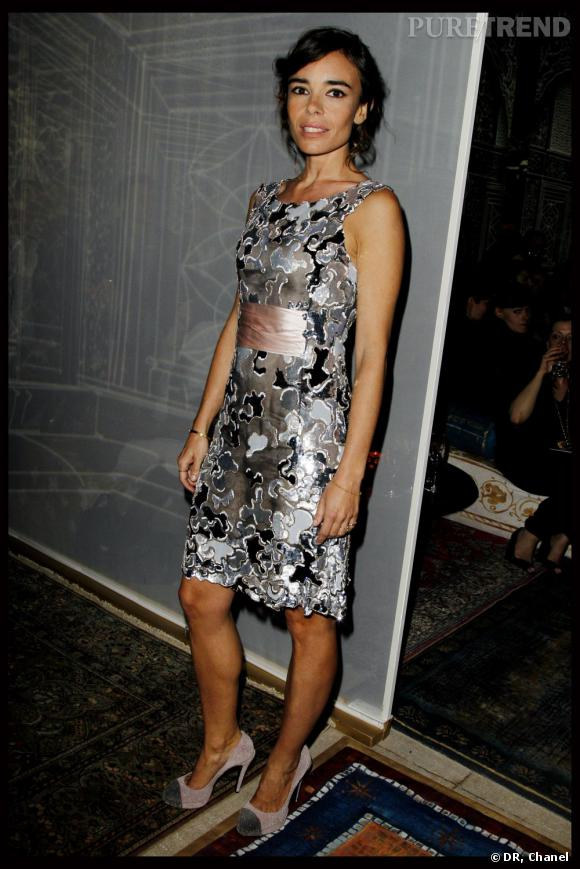 L'actrice porte une robe Chanel argentée qui flatte son teint hâlé.