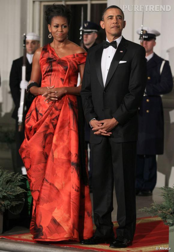 Michelle porte fidèlement le modèle comme sur le défilé, mais elle dénude une épaule pour davantage de glamour. Son look est complété par une paire de boucles d'oreilles en diamants, mises en valeur par un chignon haut.