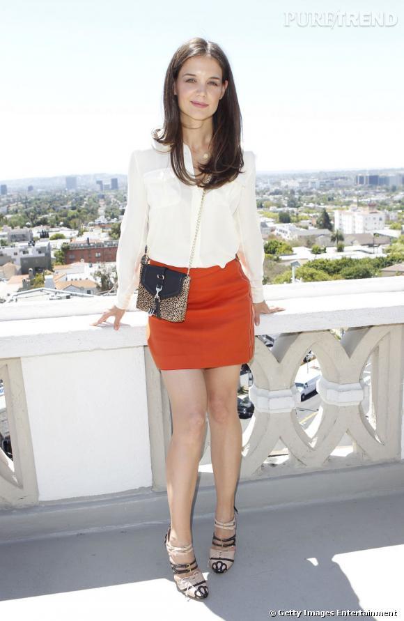 L'actrice porte une mini-jupe orange qu'elle associe à une blouse blanche.
