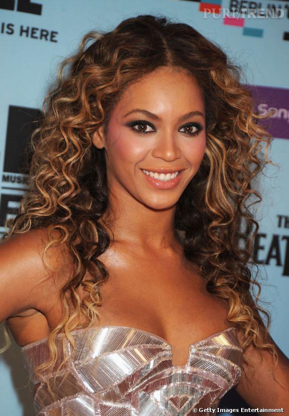 Beyoncé  adopte un maquillage soirée glamour avec un smoky eye noir. Côté bouche, elle met en valeur ses lèvres avec un gloss nacré et brillant.