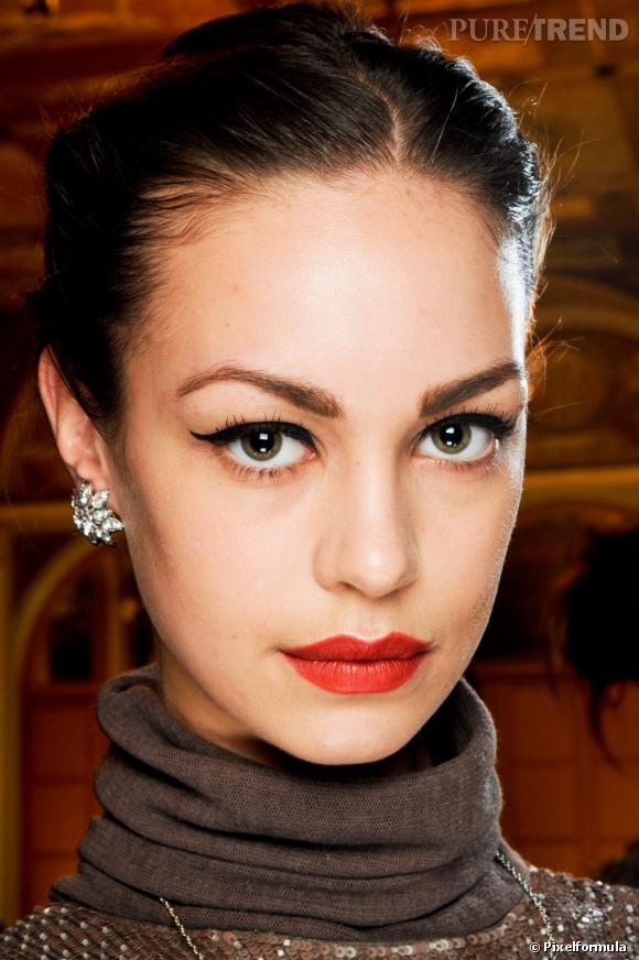Envie d'un beauty look qui mêle chic et rétro ? Osez le rouge carmin mat sur vos lèvres associé à trait d'eyeliner épais sur les yeux pour vous dessiner un oeil de biche.