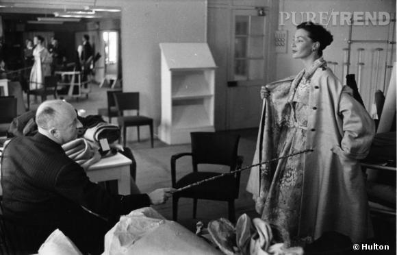 """En 1946, un certain Christian Dior s'associe avec l'homme d'affaire Marcel Boussac, et installe sa maison de couture au 30 de l'avenue Montaigne. Un an plus tard, il présente sa première collection : des robes à la taille """"étranglée"""", à contrepied de la déferlante """"zazou"""" des années 40.  Le """"New Look"""" est né, une petite révolution après des années de guerre et de privation, Christian Dior signe le retour du luxe et de la féminité.  Photo : Christian Dior dans son bureau en 1952."""