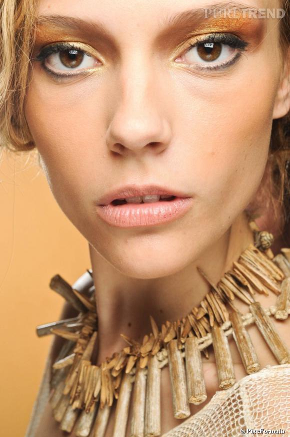 Les yeux marron se parent d'un voile d'or pour un regard précieux. Jouez sur le dégradé, du jaune au bronze, pour une paupière bijou.