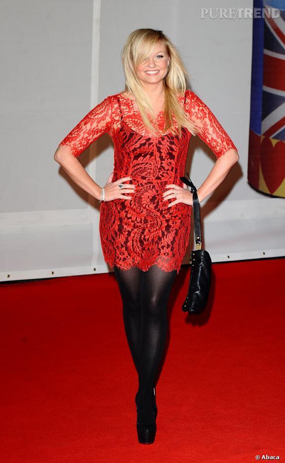Emma Bunton porte une robe en dentelle rouge doublée d'un top noir.
