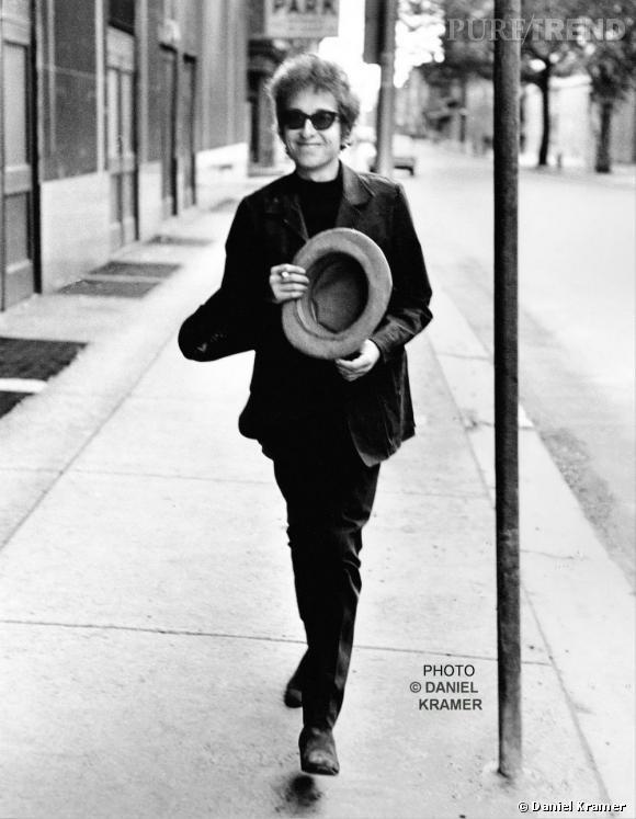 Bob Dylan cultive une image un peu dandy mais avec des détails plus hippie. Veston chemise sur un total look noir, lunettes opaques et chapeau haut de forme, voilà son style en  1694.