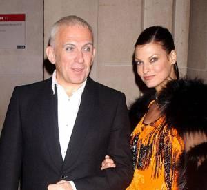 Jean-Paul Gaultier en 2003 au côté de Linda Evangelista tente cette fois-ci le maquillage. Un pantalon oversize et des talonnettes confortent son allure résolument féminine et parfaitement assumée.