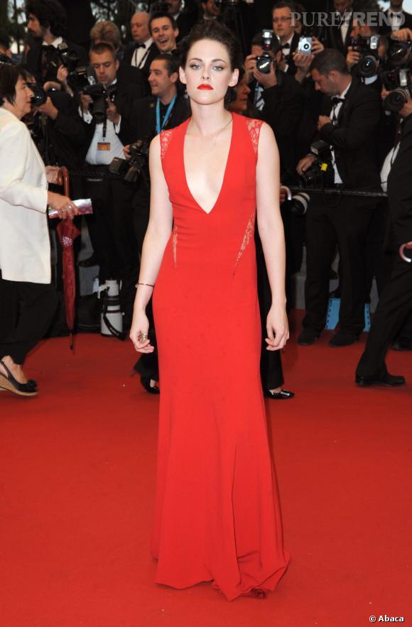 La jeune femme prend la pose dans une robe rouge séduction signée Reem Acra.
