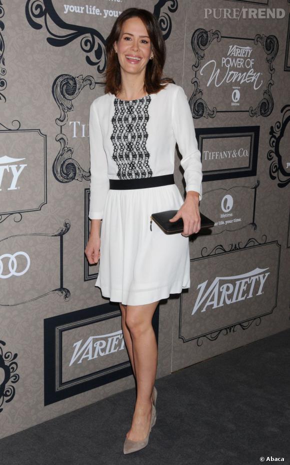 """Sarah Paulson, vue dernièrement dans la série """"American Horror Story"""", mise sur une robe immaculée ceinturée de noir."""