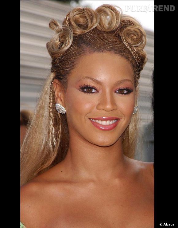 En 2001, c'est le début des expérimentations. Elle opte pour les cheveux moitié tressés, moitié lisses et une coiffure... très artistique.