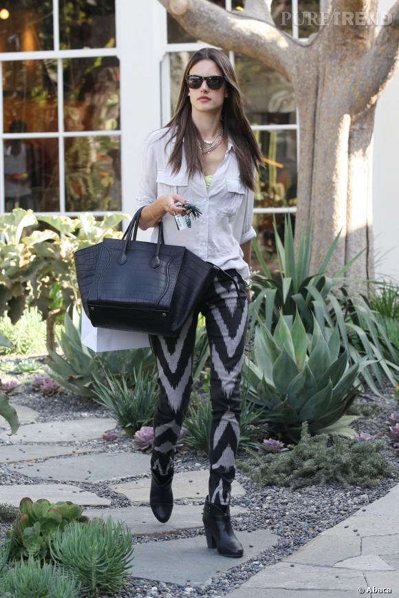 Alessandra Ambrosio mise sur un pantalon imprimé de chevrons et sur une chemise gris argile, qu'elle associe à un it-bag XXL noir.