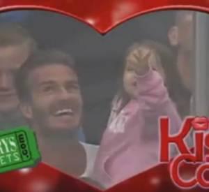 Dans la courte vidéo de la Kiss Cam, on aperçoit Harper sur le genoux de son papa. Soudain, David réalise que la caméra est braquée sur eux et fait un bisou à sa fille, tandis que cette dernière fait un coucou irrésistible.