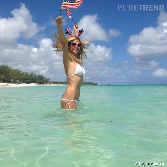 Heidi Klum nous fait rager en se prenant en photo sur une plage paradisiaque. Sable fin, mer turquoise et serre-tête aux couleurs des Etats-Unis...