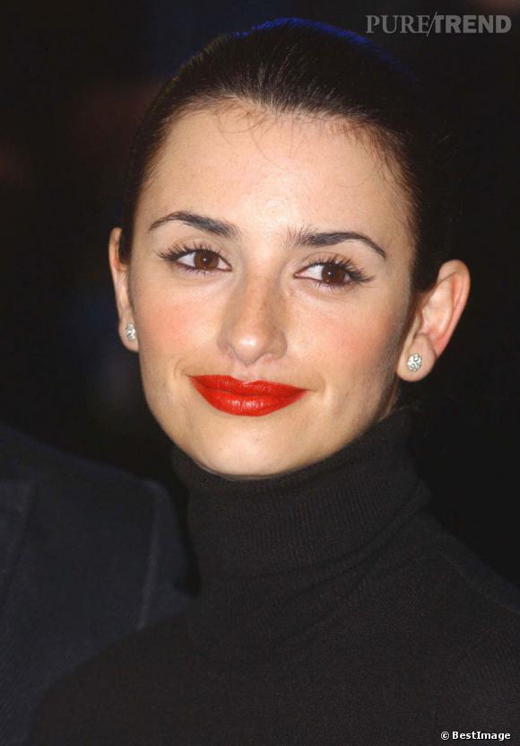 En 2002, Penelope Cruz se glamourise et opte pour une bouge écarlate et des cheveux tout plaqués. Avec sol col roulé noir... On ne voit que ses yeux.