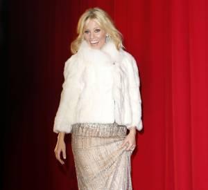 """Pour éviter les courants d'air tout en restant chic, Elizabeth Banks mise sur un épais manteau blanc pour l'avant-première de """"Hunger Games : L'Embrasement"""" à Berlin."""