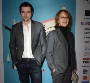 """Nathalie Baye en costume androgyne aux côtés de Raphaël Personnaz, avec qui elle partage l'affiche de """"L'Affaire Sk1""""."""