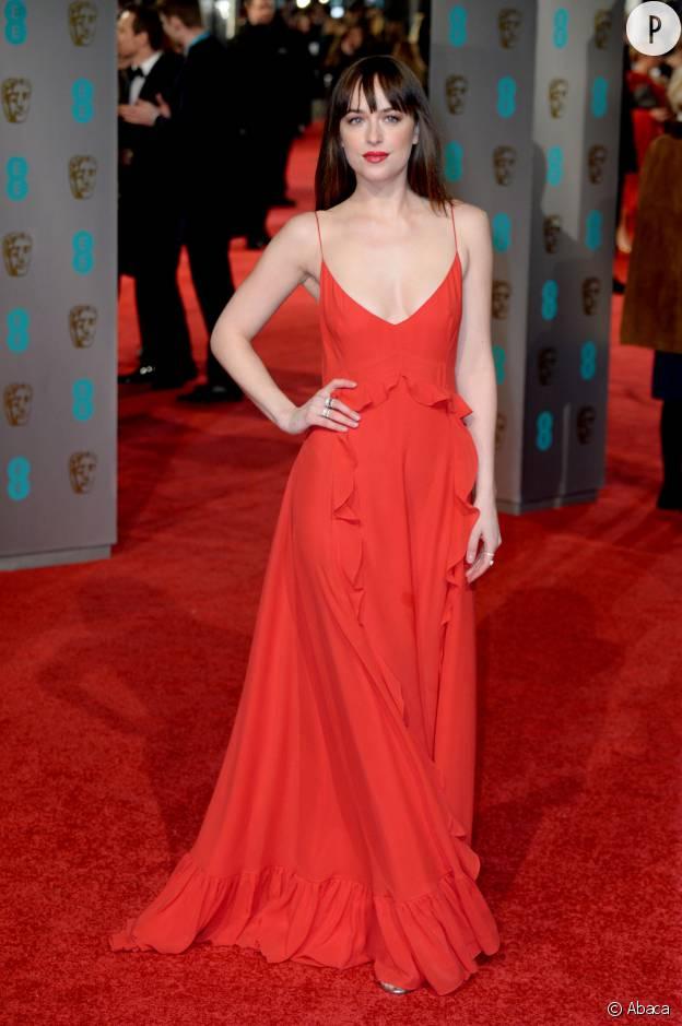 Dakota Johnson en robe rouge et chaussée de Jimmy Choo aux BAFTA Awards, ce dimanche 14 février 2016.