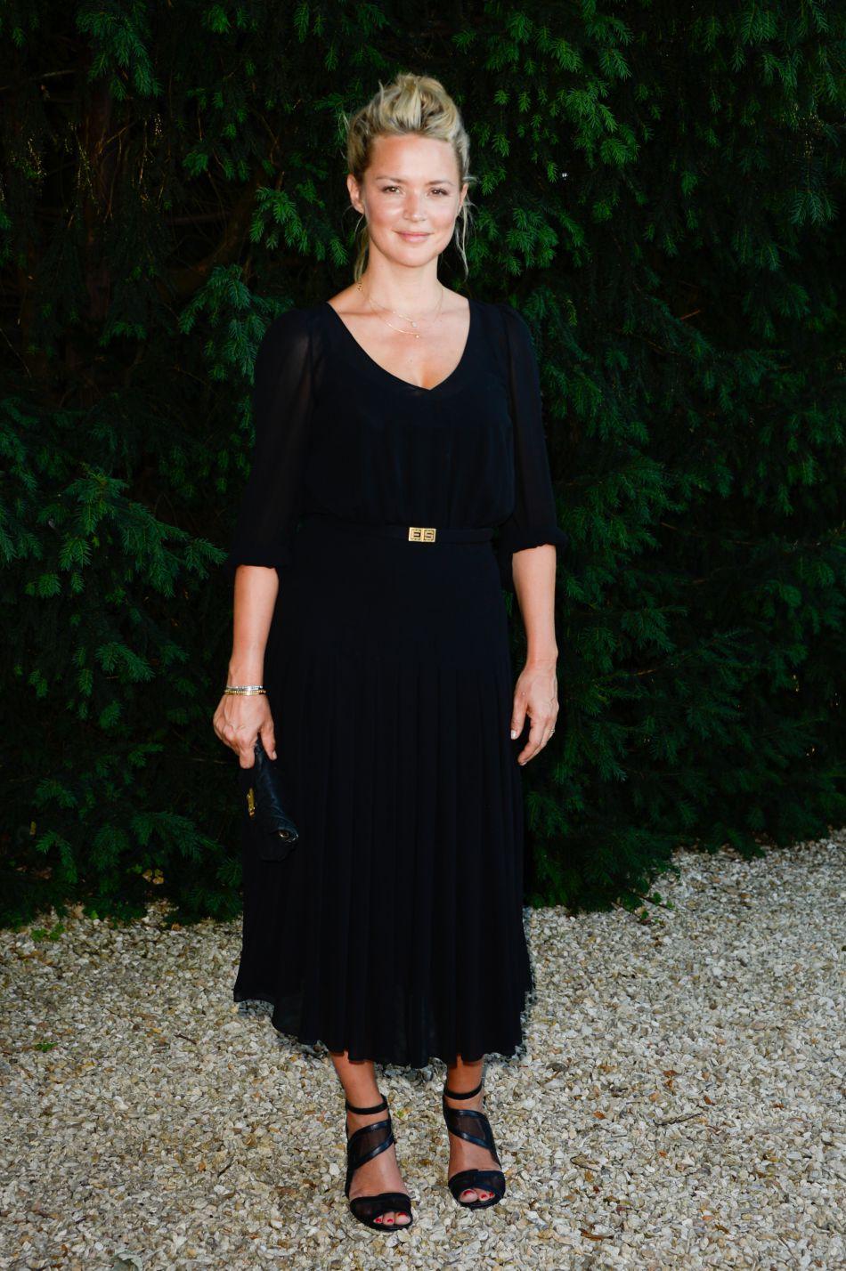 Virginie Efira accessoirise sa tenue de sandales noir et d'une pochette de la même teinte.