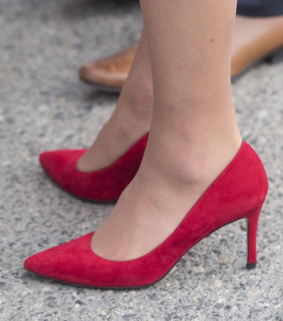Kate Middleton agrémente son look d'une paire d'escarpins rouges.