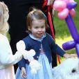 La princesse Charlotte joue avec un chien nommé Moose lors d'une fête pour les enfants des familles de militaires à la maison du Gouverneur à Victoria, le 29 septembre 2016.