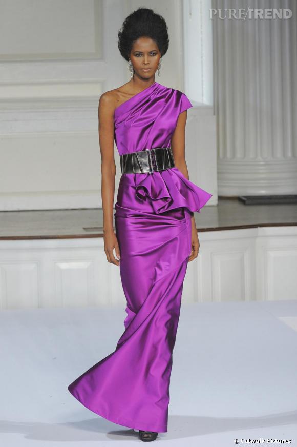 """Chez  [brand=4294736908] Oscar de la Renta [/brand]  , le violet se porte chic. Drapé avec élégance, il booste la forme classique d'une robe de soirée """"one shoulder"""". Ce qui aurait pu être archi classique en noir ou taupe, se révèle ici moderne et audacieux."""