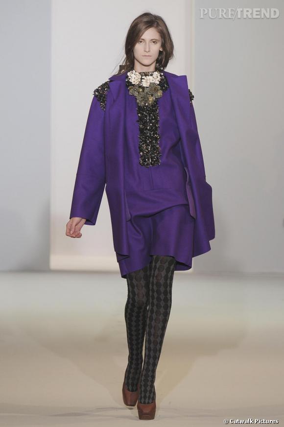 Chez  [brand=4294924650] Marni [/brand]  , le violet est franc et citadin. Il habille une silhouette résolument moderne par ses coupes droites. Accessoirisé de bijoux art déco et d'un collant pied-de-poule, le violet devient une couleur urbaine par excellence.