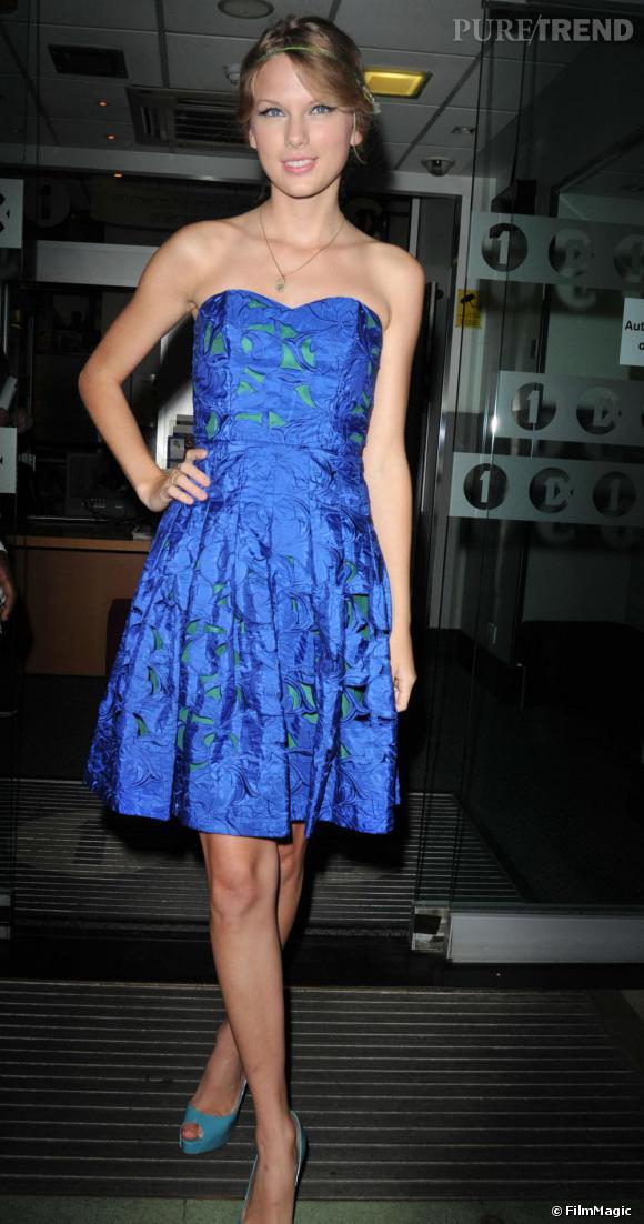 Taylor Swift ne craint pas les mélanges de couleurs. La chanteuse adopte une robe bustier bleu électrique, superposée à un tissu vert et assortie à des escarpins turquoises. Une silhouette pop.