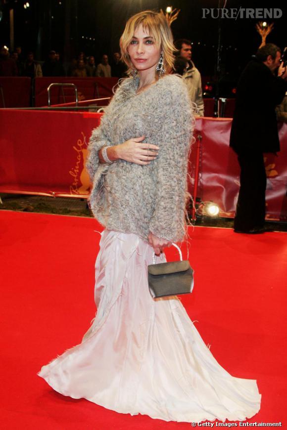 Lorsqu' Emmanuelle Béart sort le grand jeu sur les tapis rouges, elle reste dans son créneau baba cool mais plus chic. Robe fluide très longue, large gilet d'hiver, l'actrice féminise son look avec des boucles d'oreilles XXL et un petit sac kaki. Parfait.